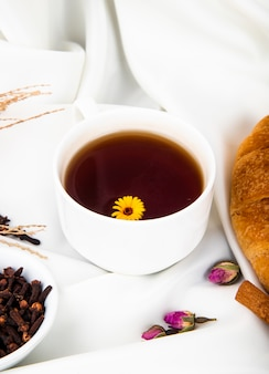 Side view of a cup of tea with croissant and cinnamon sticks and clove spice on white