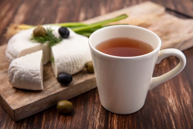 Side view cup of tea with feta cheese  with olives and green onions on a stand on a wooden background