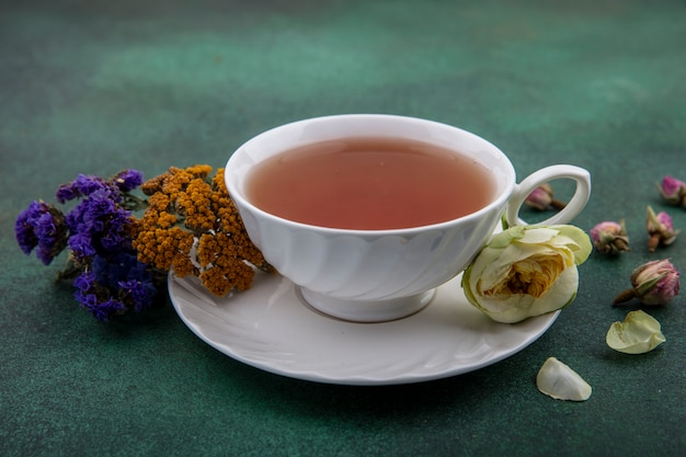 Side view cup of tea with flowers on green background