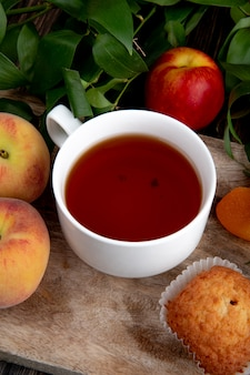 Side view of a cup of tea with fresh peaches and green leaves on wooden background
