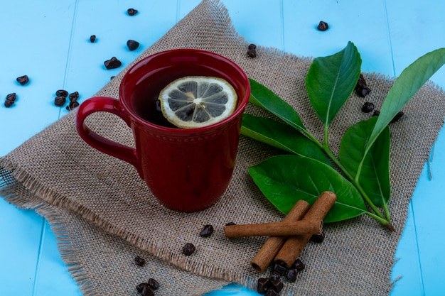 Side view of cup of tea with lemon slice and cinnamon with leaves and chocolate pieces on sackcloth on blue background