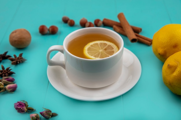 Side view of cup of tea with lemon slice and cinnamon with nuts walnut lemons and flowers on blue background