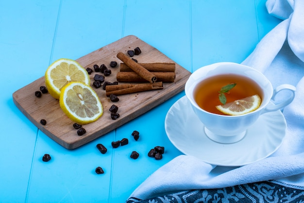 Side view of cup of tea with lemon slice on cloth and cinnamon lemon slices and chocolate pieces on cutting board on blue background