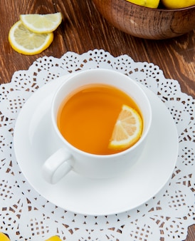 Side view of cup of tea with lemon slice in it on paper doily and lemons on wooden background