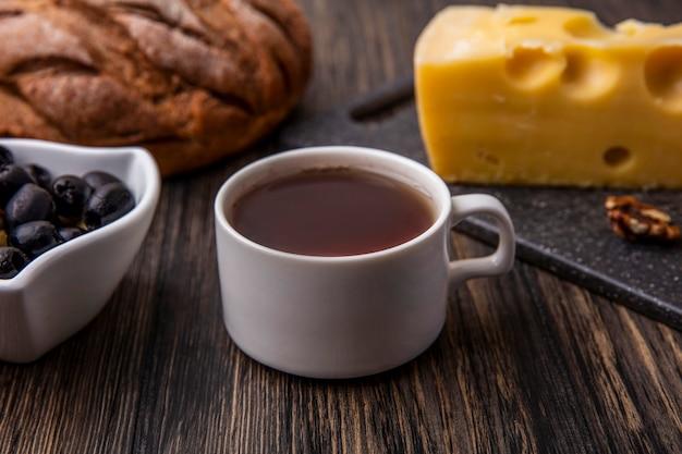 Vista laterale tazza di tè con formaggio maasdam su un supporto con olive e pane nero sul tavolo