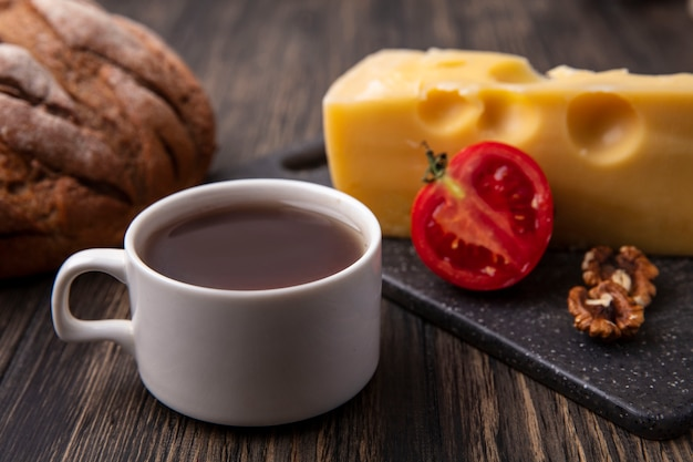 Side view cup of tea with maasdam cheese and tomato on a stand and black bread on the table