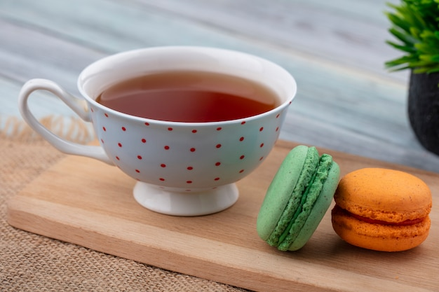 Side view of cup of tea with macarons on a cutting board
