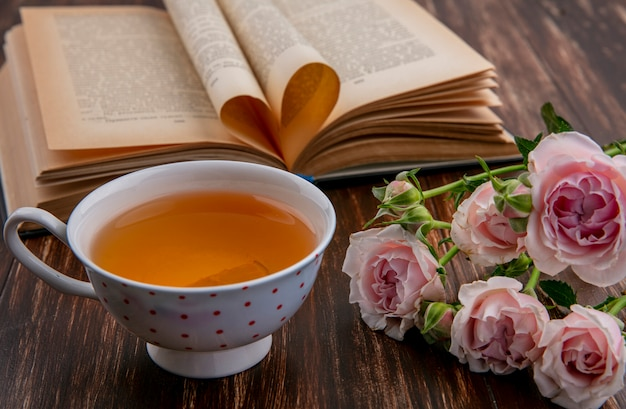 Side view of cup of tea with open book and pink roses on wooden surface