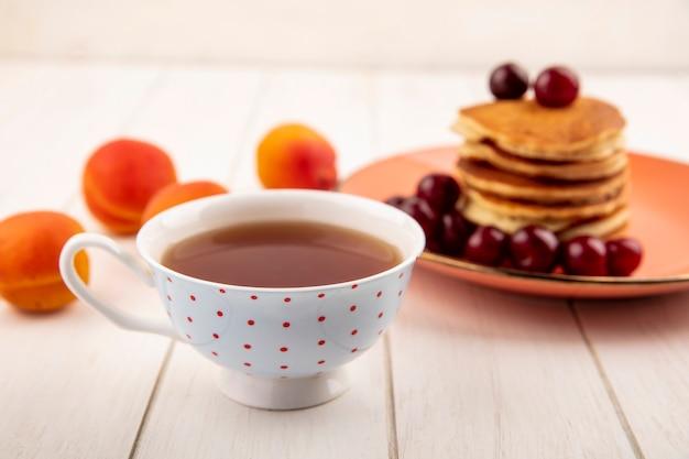 Vista laterale della tazza di tè con piatto di frittelle e ciliegie e albicocche su fondo di legno