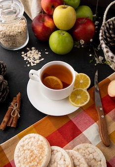 Side view cup of tea with sliced lemon and cinnamon with apples and a knife on the table