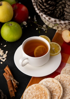 Side view cup of tea with sliced lemon and cinnamon with apples on the table