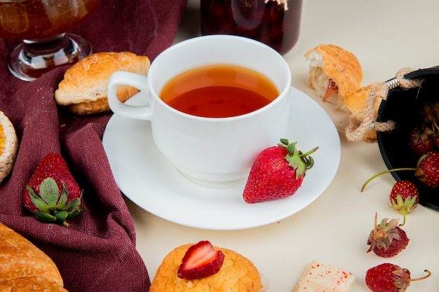 Side view of cup of tea with strawberries rolls cupcake jam chocolate on white table