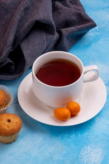 Side view of a cup of tea with tasty muffin on blue table