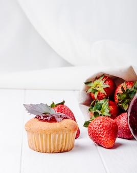いちごジャムバジルと白い背景の上に新鮮なイチゴの側面図カップケーキ