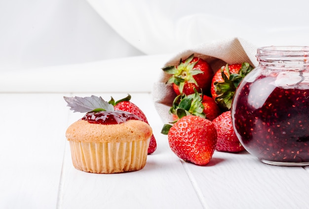 Side view cupcake with strawberry jam basil and fresh strawberry on white background