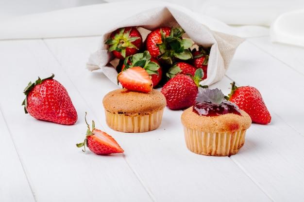 いちごジャムバジルと白い背景の上に新鮮なイチゴのサイドビューカップケーキ