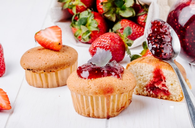 Side view cupcakes with strawberry jam basil and fresh strawberry on white background