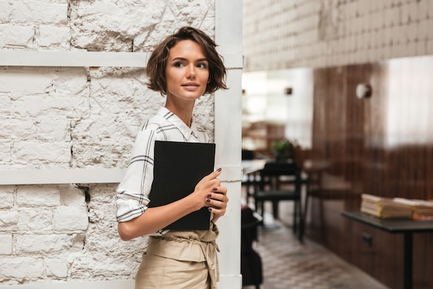 Side view of curly female manager holding folder in hand