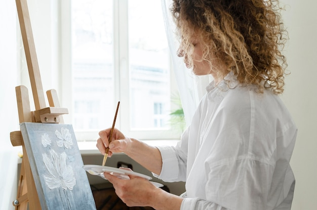 Side view of curly-haired woman painting at home