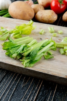 Side view of cut celery on wooden surface and background with copy space