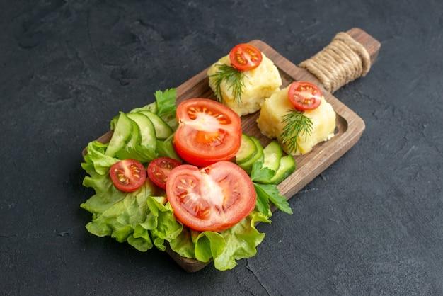 Vista laterale del taglio di pomodori freschi e cetrioli formaggio su tavola di legno su superficie nera