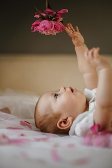 Side view of cute baby girl lying on bed and seriously trying catch dim pink peony