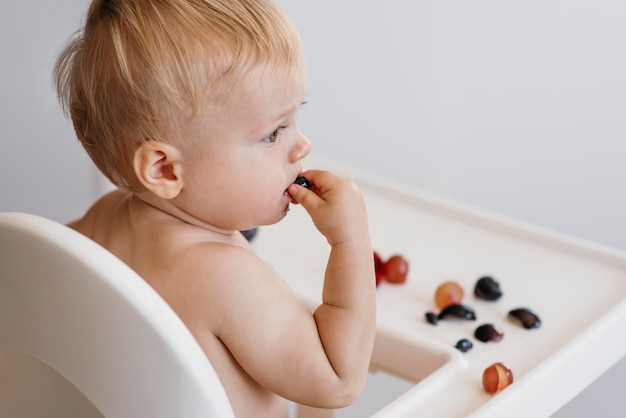 Вид сбоку милый ребенок в стульчике, выбирая, какие фрукты съесть