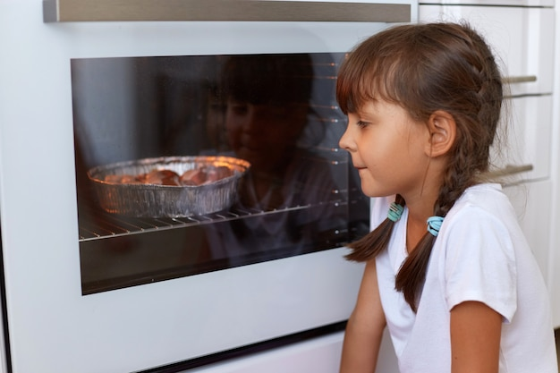Side view of cute dark haired girl wearing white t shirt waiting for baking muffins or cupcakes near oven, looking at tasty fruitcake in gas-stove, cooking process on kitchen.