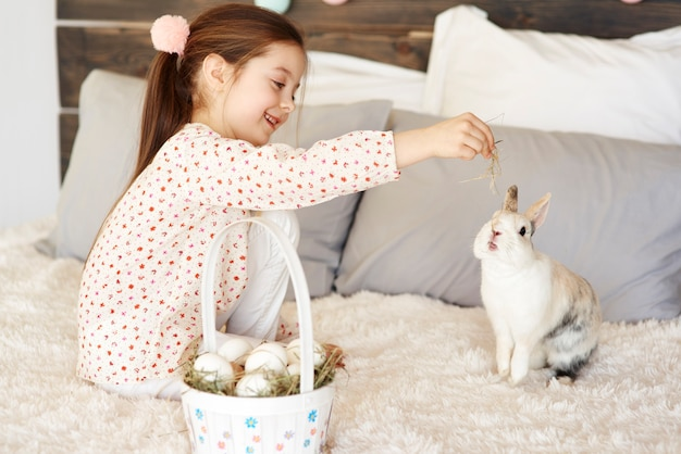Side view of cute girl feeding the rabbit