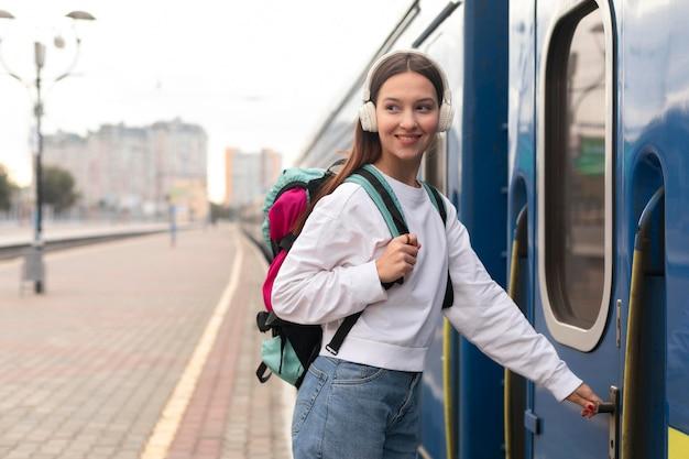 Ragazza carina vista laterale alla stazione ferroviaria di entrare nel treno