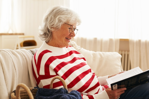 Side view of cute happy grandmother in glasses enjoying reading indoors, sitting on sofa with interesting detective story, smiling joyfully. stylish elderly woman relaxing on couch holding book