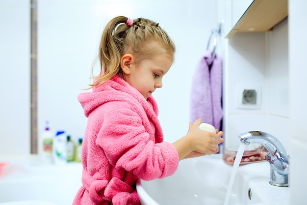 Side view of cute little girl with ponytail in pink bathrobe washing her hands.