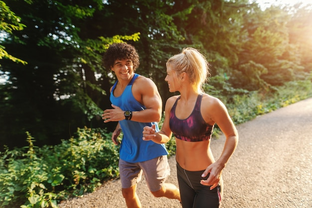 Side view of cute sporty couple running in nature on the sunny summer day.
