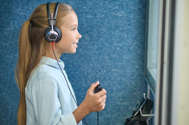 Side view of a cute young female patient in audiometer headsets standing in the soundproof booth