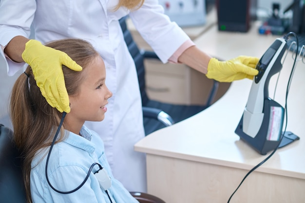 Side view of a cute young patient undergoing an audiometric test performed by an experienced medical professional