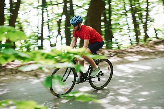 側面図。自転車のサイクリストは晴れた日に森のアスファルト道路に