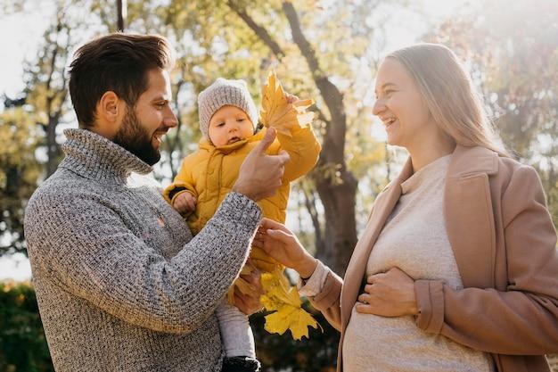Vista laterale di papà e madre con bambino all'aperto