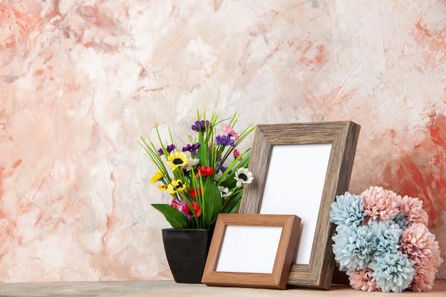 Vista laterale di cornici per foto in legno vuote marrone scuro e bellissimi fiori sul lato sinistro su superficie di colori misti