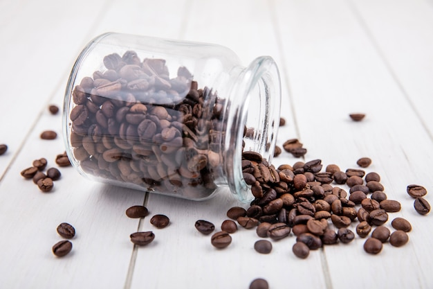 Side view of dark roasted coffee beans falling out of a glass jar on a white wooden background