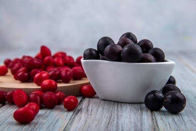 Vista laterale del prugnolo dalla pelle scura su una ciotola bianca con bacche di corniolo rosso isolato su una tavola di cucina in legno su un fondo di legno grigio