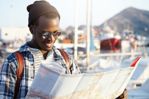 Side view of dark-skinned tourist with backpack in trendy hat and sunglasses examining directions using his paper road map. yacht park or club in picturesque resort town