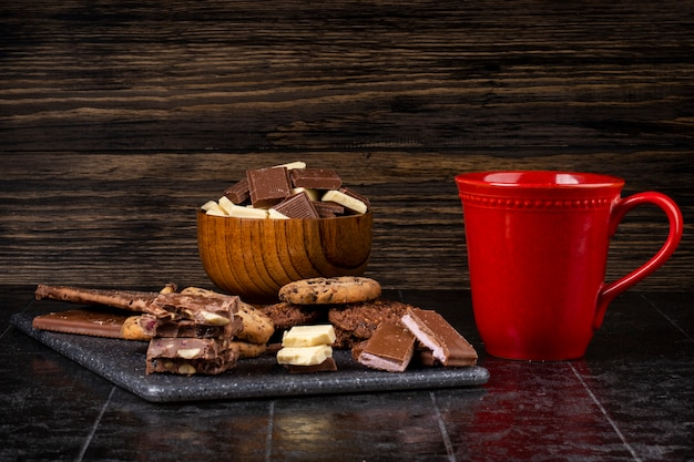 Side view of dark and white chocolate in a wooden bowl a cup of tea and oatmeal cookies scattered on dark background