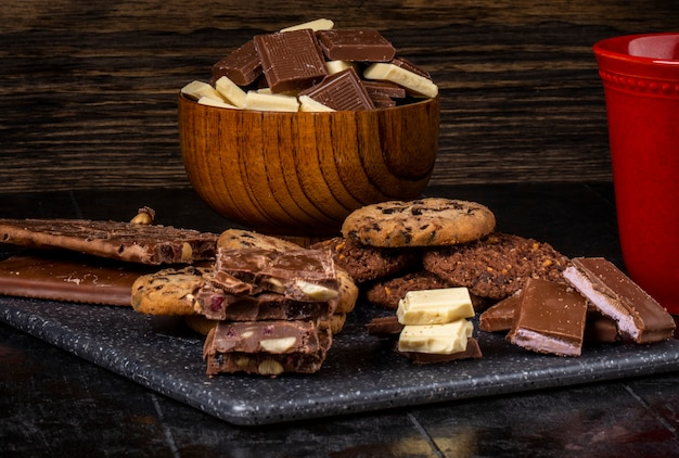 Side view of dark and white chocolate in a wooden bowl and oatmeal cookies scattered on dark background