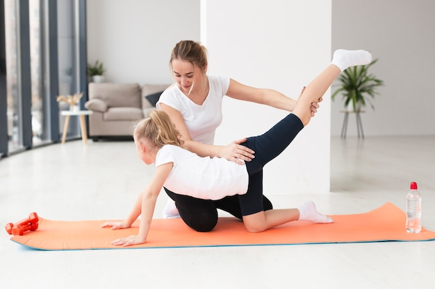 Side view of daughter working out with mother at home