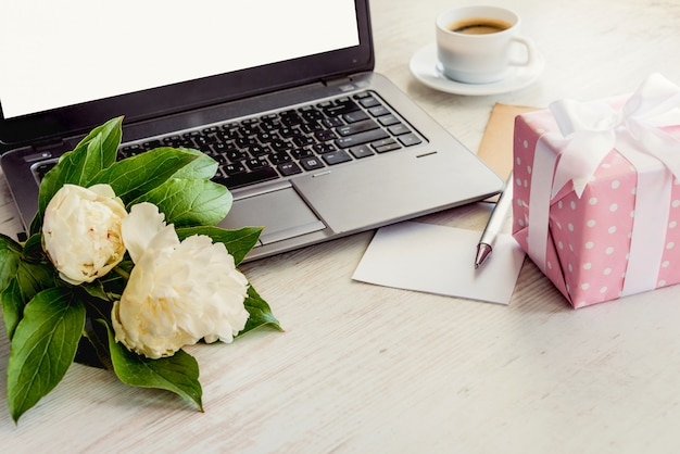 Side view of a deck with computer, bouquet of peonies flowers, cup of coffee, empty card and pink dotted gift box.