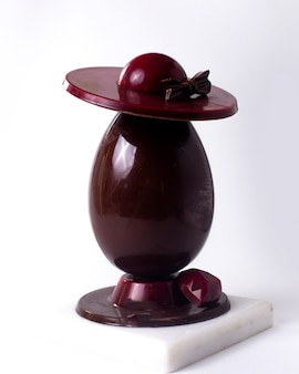 Side view decorated chocolate egg with a hat and a chocolate heart on stand