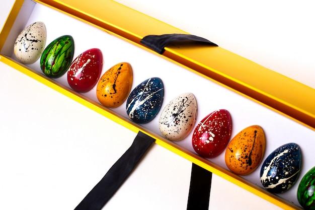 黄色のオープンボックスで装飾されたマルチカラーチョコレートの卵