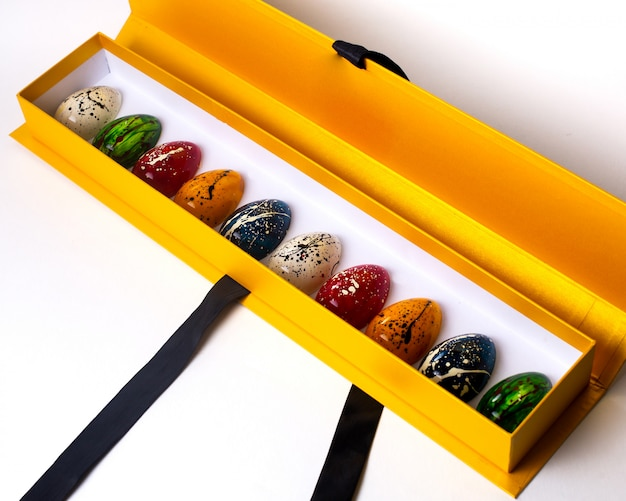 Side view decorated multi colored chocolate eggs in a yellow open box