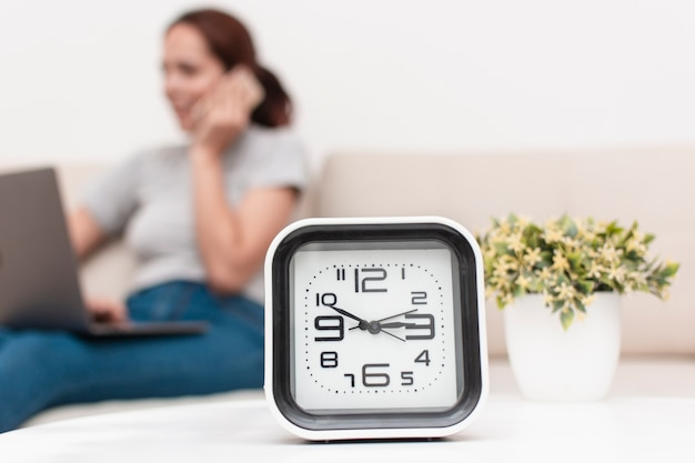 Side view of defocused woman talking on the phone with clock