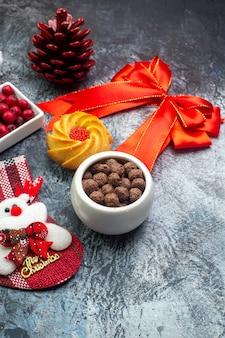 Vista laterale di deliziosi biscotti e corniolo su un piatto bianco nuovo anno calzino rosso cono di conifere nastro rosso su superficie scura